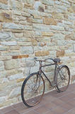 Oggetto d'antiquariato o retro bicicletta ossidata fuori su una parete di pietra Fotografia Stock