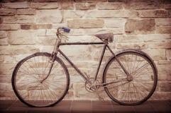 Oggetto d'antiquariato o retro bicicletta ossidata fuori su una parete di pietra Immagine Stock Libera da Diritti
