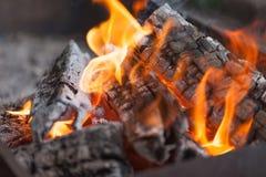 Ogień z węglami drzewnymi płonący drewna Makro- Żyje płomienie z dymem Drewno z płomieniem dla grilla i kulinarnego bbq jasny kol fotografia royalty free