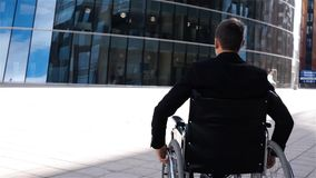 Ogiltig affärsman i rullstolflyttning nära modernt affärscentrum stock video