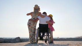 Ogiltigt folk i panelljuset, pappa i rullstol som kramar dottern på blå himmel för bakgrund, rörelsehindrad man lager videofilmer
