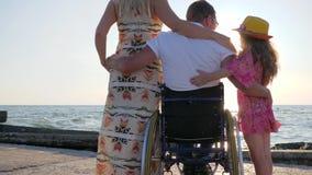 Ogiltigt med gravida kvinnan och barnet på bakgrundshavet, make i rullstol arkivfilmer
