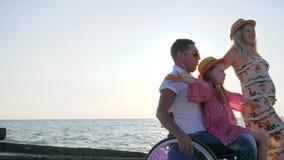 Ogiltigt på sommar, familjlek tillsammans på blå himmel för bakgrund, liten flickasammanträde på pappa i rullstol med stock video