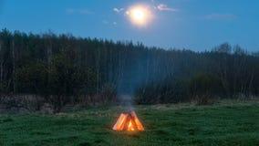Ognisko w polu w tle księżyc Zdjęcie Stock