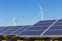 Ogniwa słoneczne z silnikami wiatrowymi wytwarza elektryczność w hybrydowej elektrownia systemów staci na niebieskiego nieba tle zdjęcia royalty free