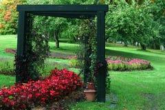 Ogród z drewnianym łukiem i kwiaty obok glinianych garnków zdjęcie stock