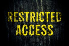 Ograniczony dojazdowy ostrzegawczy niebezpieczeństwo podpisuje wewnątrz żółtych listy malujących nad ciemną grungy cementową beto zdjęcia stock