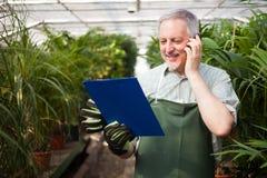Ogrodniczka opowiada na telefonie Obrazy Stock