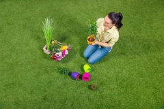 Ogrodniczka siedzi na zielonej trawie z roślinami i flowerpots Obraz Royalty Free