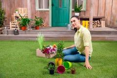 Ogrodniczka siedzi na zielonej trawie z roślinami i flowerpots Obraz Stock