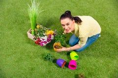Ogrodniczka siedzi na zielonej trawie z roślinami i flowerpots Zdjęcie Royalty Free