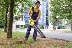 Ogrodniczka używa jego liść dmuchawę w ogródzie Zdjęcia Royalty Free