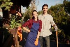 Ogrodniczki ładna dziewczyna w facecie z łopaty stojakami w cudownym ogródzie na słonecznym dniu i fartuchu obraz stock