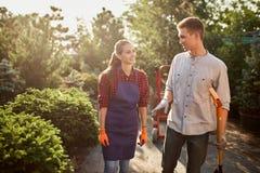 Ogrodniczki ładna dziewczyna w facecie z łopaty odprowadzeniem na ogrodowej ścieżce w cudownym ogródzie na słonecznym dniu i fart zdjęcia stock