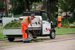 Ogrodniczki zrywanie cutted trawy i nieżywych liści w miastowym parku zdjęcia stock
