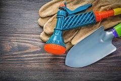 Ogrodowe kiści nozzle zbawcze rękawiczki wręczają rydel na drewnianej desce agr Obraz Royalty Free