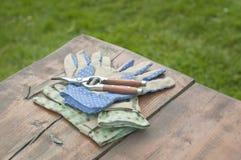 Ogrodowe rękawiczki i cążki na stole Zdjęcia Royalty Free