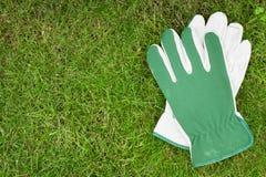 Ogrodowe rękawiczki nad zieloną trawą Zdjęcia Royalty Free