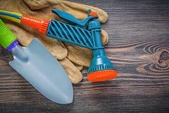 Ogrodowe wodnej krócicy zbawcze rękawiczki wręczają rydel na drewnianej deski gar Obrazy Stock