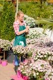 Ogrodowego centrum kobieta pisze notatka puszkujących kwiaty zdjęcia royalty free