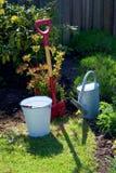 Ogrodowego narzędzia łopaty podlewania puszki wiadra stara cynkowa torba w ogródzie z kwiatami i trawą pojęcia ogrodnictwo Obrazy Stock