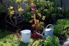 Ogrodowego narzędzia łopaty podlewania puszki wiadra stara cynkowa torba w ogródzie z kwiatami i trawą pojęcia ogrodnictwo Zdjęcia Stock