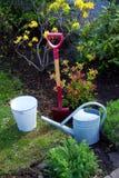 Ogrodowego narzędzia łopaty rydla podlewania puszki wiadra stara cynkowa torba w ogródzie z kwiatami i trawą Fotografia Stock