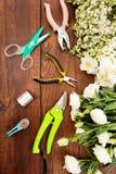 Ogrodowi narzędzia, narzędzia dla florystyk i kwiaty na drewnianym stole, Fotografia Royalty Free