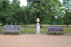 Ogrodowy ornament na piedestale drewnianych ławkach i, siedzenie Fotografia Stock