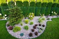 Ogrodowy szczegół: kwiatu łóżko z otoczakami i roślinami Obraz Stock
