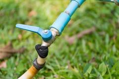 Ogrodowy wąż elastyczny lub biała gumowa tubka z faucet na trawy polu Zdjęcia Royalty Free