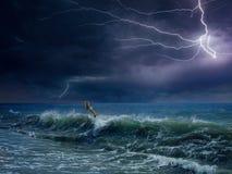 Ogromna błyskawica w ciemnym niebie nad burzowy morze fotografia stock
