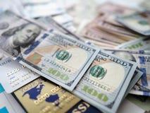 Ogromna ilość USA banknoty kłama przy stołem wśród paszportowych bankowość kart i pieniężnego raportu obrazy stock