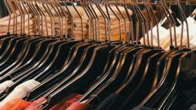 Ogromna liczba kobiety odzież różni kolory wiesza na wieszakach i kłama na półkach w sklepie odzieżowym zbiory