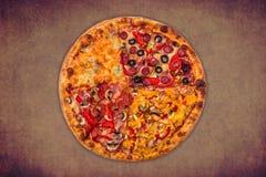 Ogromna międzynarodowa pizza na czerwonym tle Zdjęcia Stock