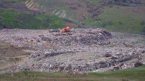 Ogromna pomarańczowa śmieciarska ciężarówka nalewa grat na toksycznym śmieciarskim usypie zbiory