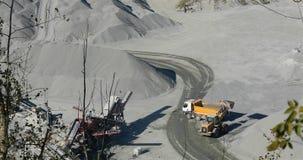 Ogromni żółci buldożeru pickup ładowania kamienie w ciężarówkę, żółty buldożer ładują granit z tyłu usyp ciężarówki zdjęcie wideo