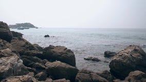 Ogromni popielaci plaża kamienie przeciw falistemu krystalicznemu oceanowi z statkami zbiory