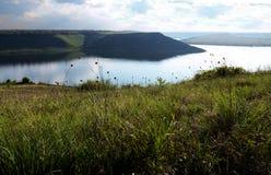 Ogromni rzeczni Dniester przepływy między wysokością moczą wzgórza zakrywających z wiosny luksusową zieloną trawą przeciw niebies fotografia royalty free