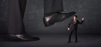 Ogromny nogi kroczenie na malutkim businnessman pojęciu Zdjęcie Stock