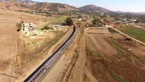 Ogromny nowożytny miastowy pociąg pasażerski rusza się przez suchego pustynnego jaru w piaska stepu krajobrazie w 4k trutnia powi zbiory wideo