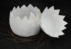 Ogromny papier - mache jajko w gniazdeczku gałąź odkrywa w dwa częściach na czarnym tle Zdjęcia Stock