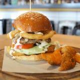 Ogromny wołowina hamburger z cebulą smażącą i pomidorem na drewnianym talerzu Obrazy Stock