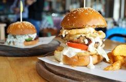 Ogromny wołowina hamburger z cebulą smażącą i pomidorem na drewnianym talerzu Obrazy Royalty Free