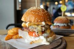 Ogromny wołowina hamburger z cebulą smażącą i pomidorem na drewnianym talerzu Zdjęcia Royalty Free