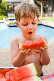 Oh the joys of watermelon. Young boy eating watermelon and swiming, having fun at a summer swim party Royalty Free Stock Images