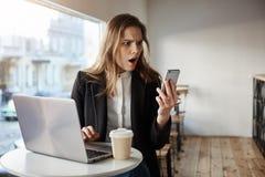 Oh mein, bin ich für Arbeit spät Porträt der entsetzten und überraschten stilvollen Frau im Café, sitzend nahe Laptop und dem Tri Lizenzfreies Stockfoto