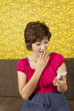 Oh my god!. Female acting excited on her smartphone Stock Photo