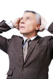 Oh my god!. Frustrated mature man in formalwear holding head in hands and looking up while standing against white background Stock Images