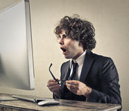 Oh my God. Man in front of a computer looks astonished and surprised Royalty Free Stock Photos